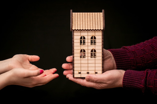 A man gives a woman a wooden toy house. housing as a gift