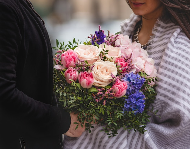 Мужчина дарит женщине букет из смешанных цветов