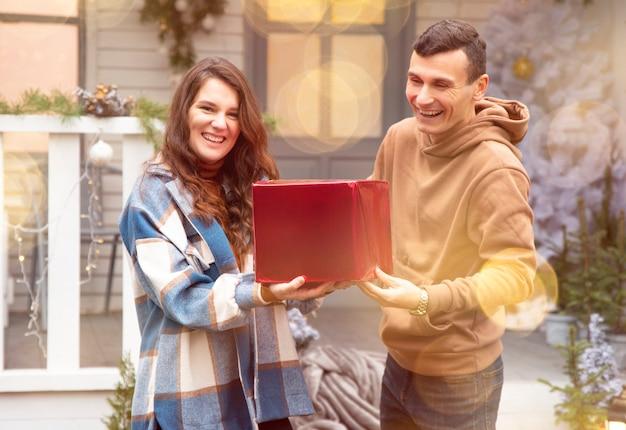 Мужчина делает рождественский подарок своей девушке. они держат красную коробку с подарком на день святого валентина.