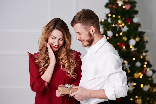 Мужчина делает рождественский подарок женщине