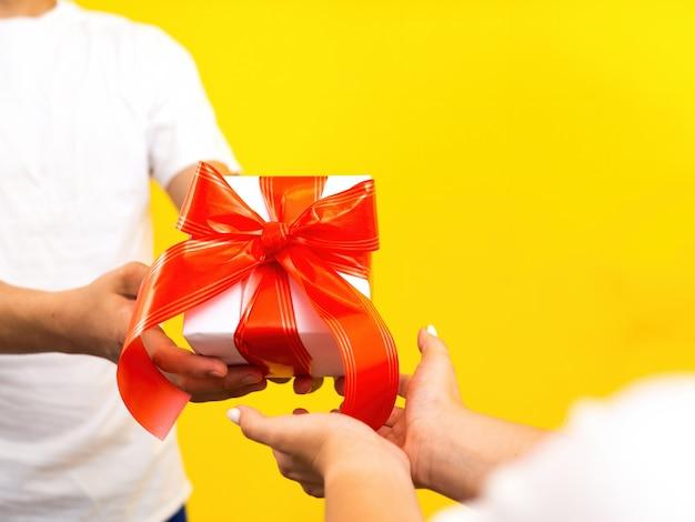 Мужчина дает женщине подарочную коробку с бюрократической лентой