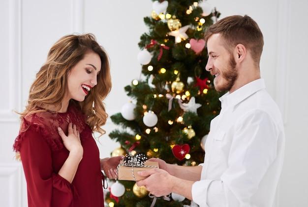 Мужчина делает подарок удивленной женщине