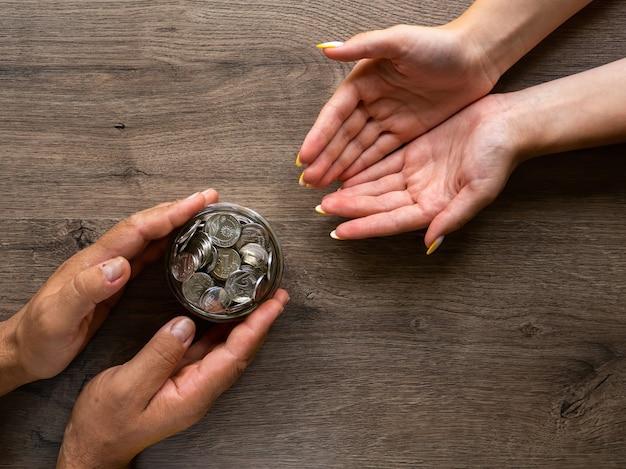 Мужчина дает женщине банку с металлическими монетами