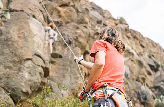 Man giving assistance to woman who is climbing up on mountain cliff