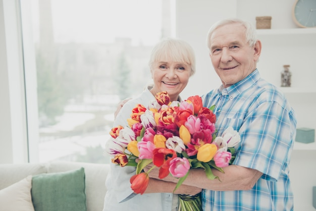 Man giving a bouquet of flowers to his wife
