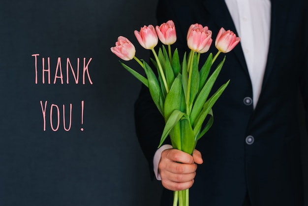 Man giving a bouquet of pink flowers tulips. greeting card with text thank you