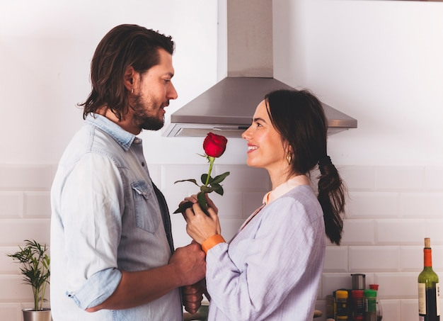Man giving bright rose to woman in kitchen