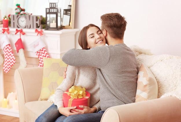 Человек дает коробку рождественского подарка своей девушке в помещении