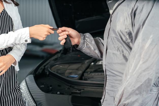 Мужчина дает клиенту ключи от ее отремонтированной машины в автосервисе