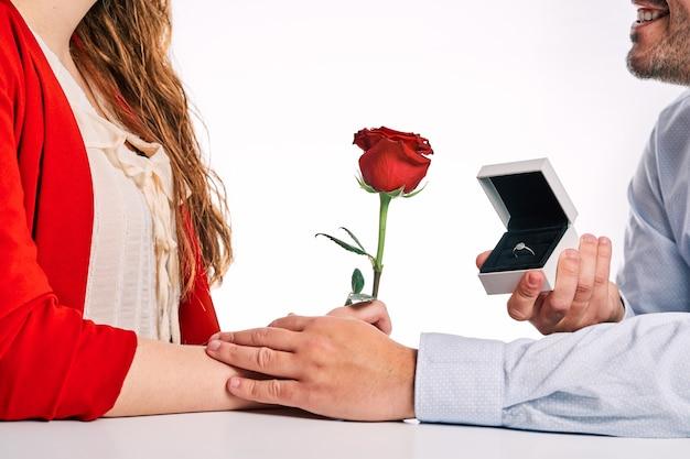 彼のパートナーと赤いバラに婚約指輪を与える男。バレンタインデーのコンセプト、恋愛とプロポーズのカップル。
