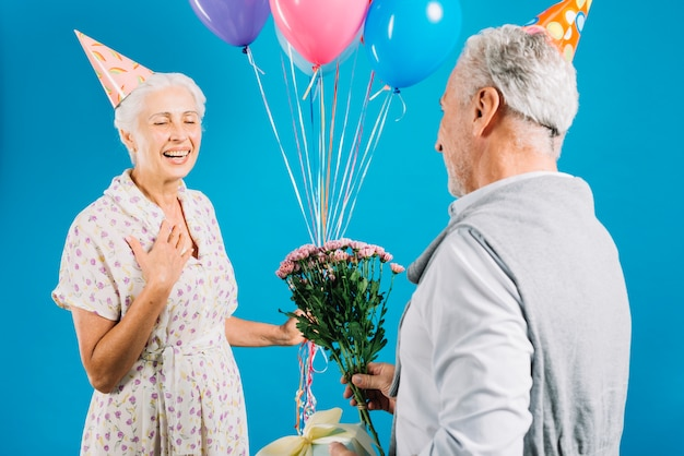 Man giving flower and birthday gift to her wife