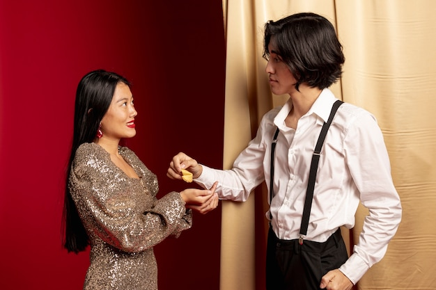 Man giving fortune cookie to woman for chinese new year
