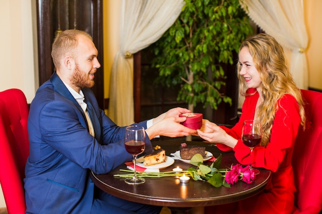Man giving gift box in heart shape to woman at table
