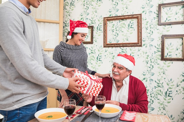 Man giving gift box to old man in red santa hat