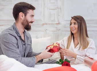 Man giving gift box to woman in bed