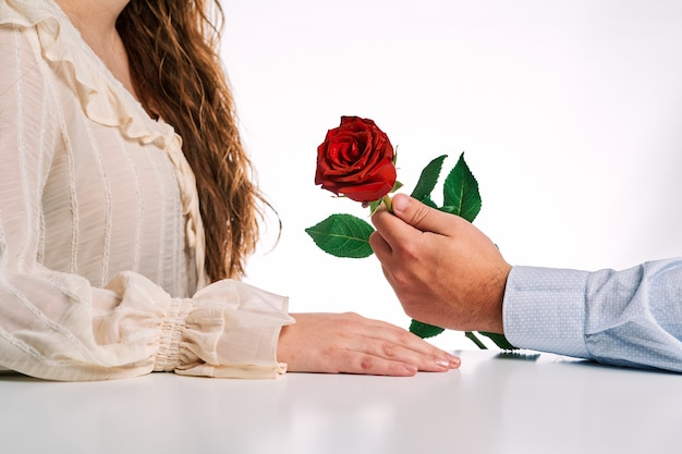 Man giving a gift of a red rose to his partner. concept of valentine's day, couple in love and marriage.