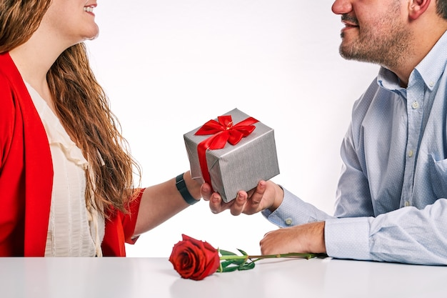 Man giving a gift and a red rose to his partner. concept of valentine's day and couple in love.