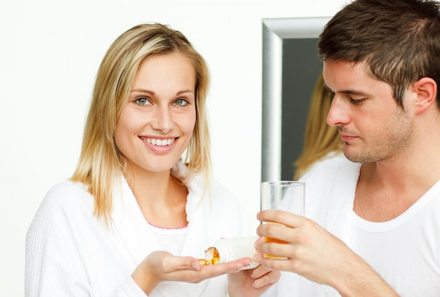 Man giving a glass to his fiance for her pills