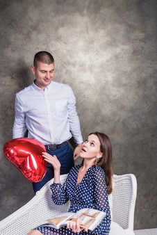 Man giving heart balloon to dissatisfied woman