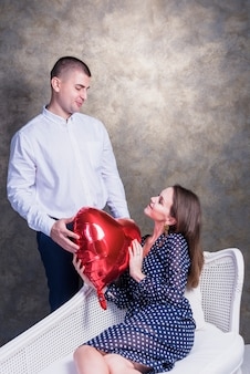 Man giving heart balloon to woman