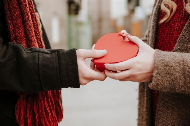 여자에게 심장 모양의 선물을주는 사람