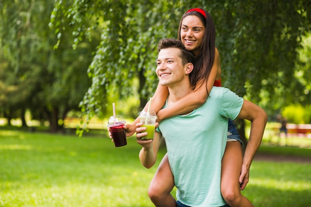 Man giving her girlfriend piggyback ride holding smoothies in the park