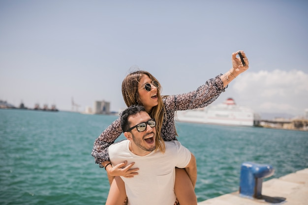Man giving her girlfriend piggyback ride taking selfie on cell phone near the sea