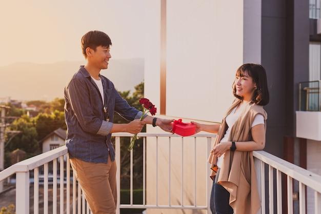 男彼のガールフレンドのハート型ボックスとバラを与えます