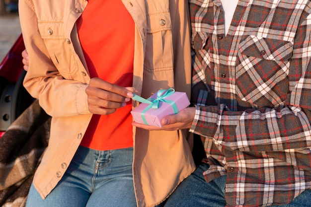 Man giving his girlfriend a wrapped gift