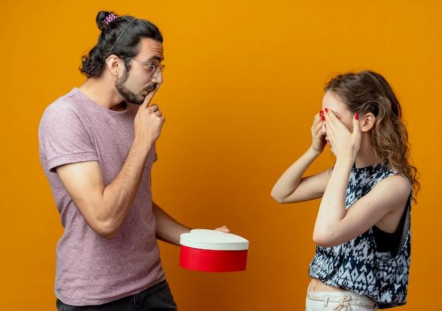 Uomo che dà sorpresa dando scatola presente alla sua ragazza frida mentre lei chiude gli occhi, giovane bella coppia uomo e donna sopra il muro arancione