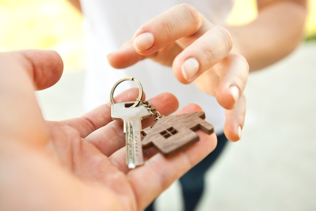 Man giving the metal key from door with wooden trinket in shape of house to the woman