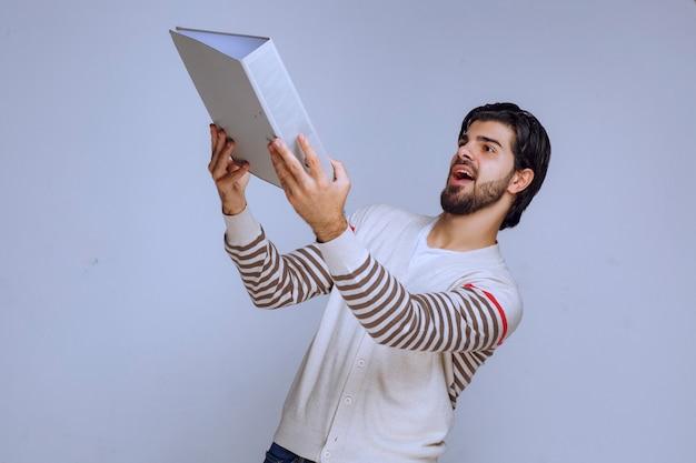 レポートフォルダを授受する男性。