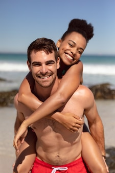 Man giving piggyback to woman on beach in the sunshine