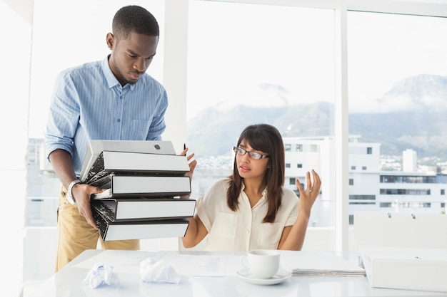 Man giving pile of files to his exasperated colleague