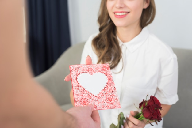 Man giving pink greeting card to woman