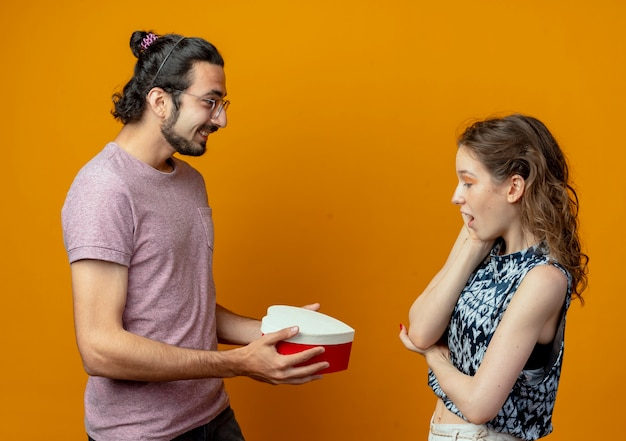 Мужчина дает подарочную коробку своей девушке, молодой красивой паре мужчина и женщины на оранжевом фоне