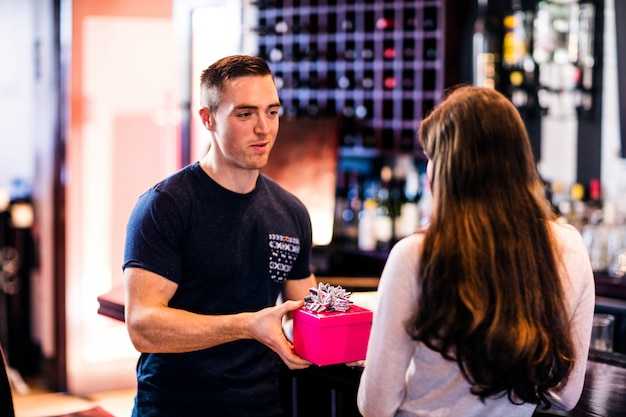 Man giving a present to his girlfriend in a bar