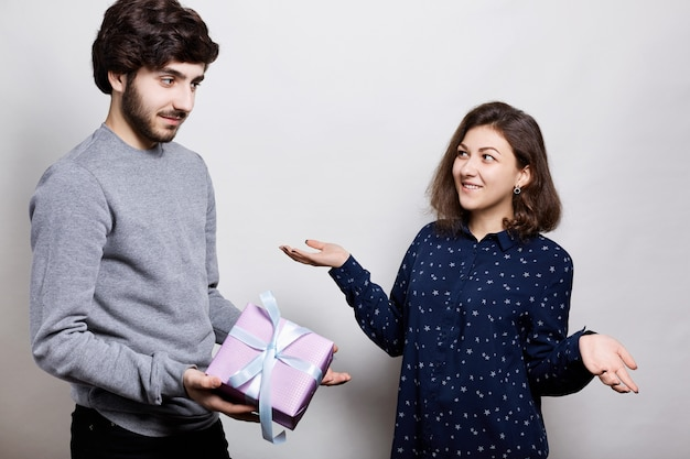 Man giving a present to his girlfriend. romantic surprise, woman receives a gift from her boyfriend