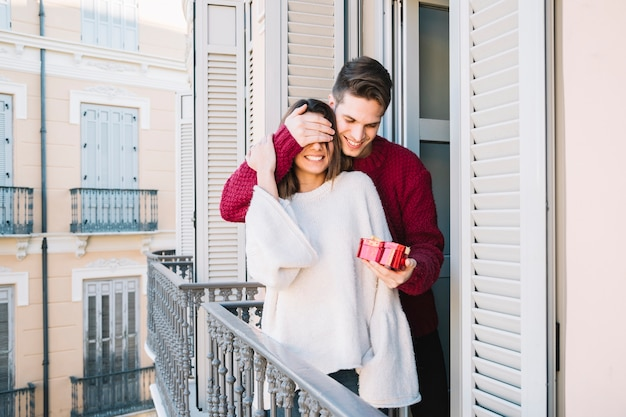 Man giving present to woman on balcony