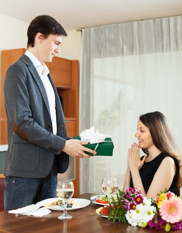 Man giving present to woman during romantic dinner