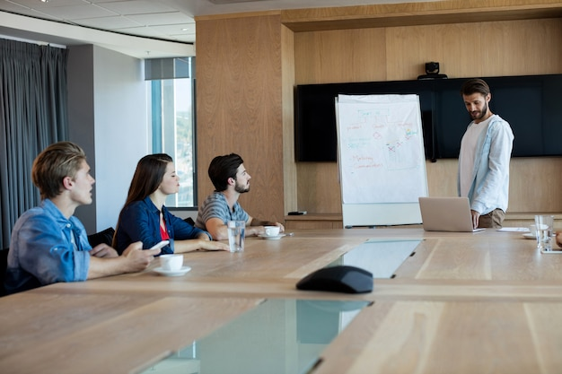 Man giving presentation to her colleagues in conference room at office