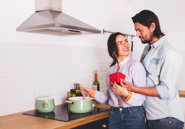 Man giving red gift box to woman in kitchen