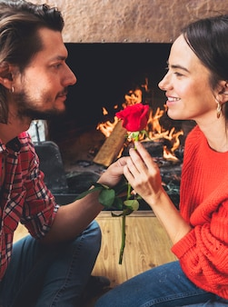 Man giving red rose flower to woman on floor