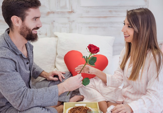 Man giving red rose to woman on bed