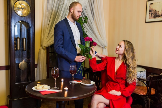 Man giving roses bouquet to woman in restaurant