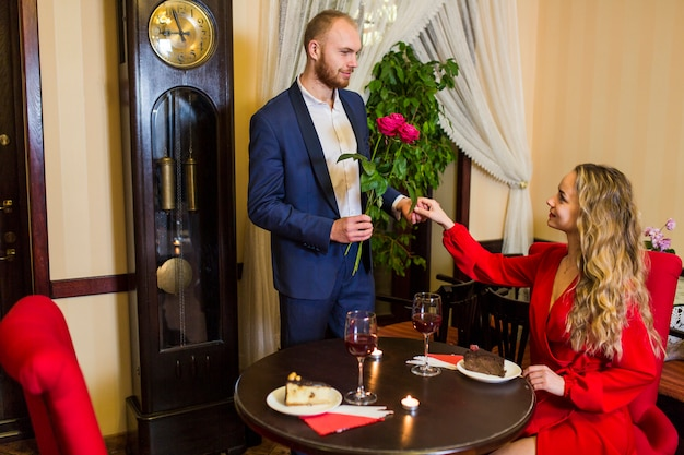 Man giving roses to woman in restaurant