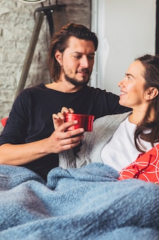 Man giving small gift box to woman on couch