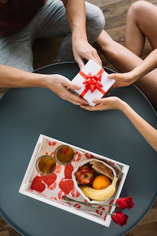 Man giving small gift box to woman