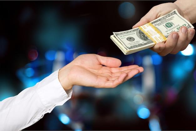 Мужчина дает стопку долларов женщине на темном размытом фоне
