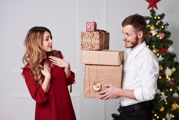 Мужчина дает стопку подарков женщине